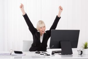 16945229-happy-businesswoman-raising-arms-at-desk